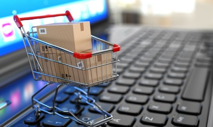 E-commerce. Shopping cart with cardboard boxes on laptop.